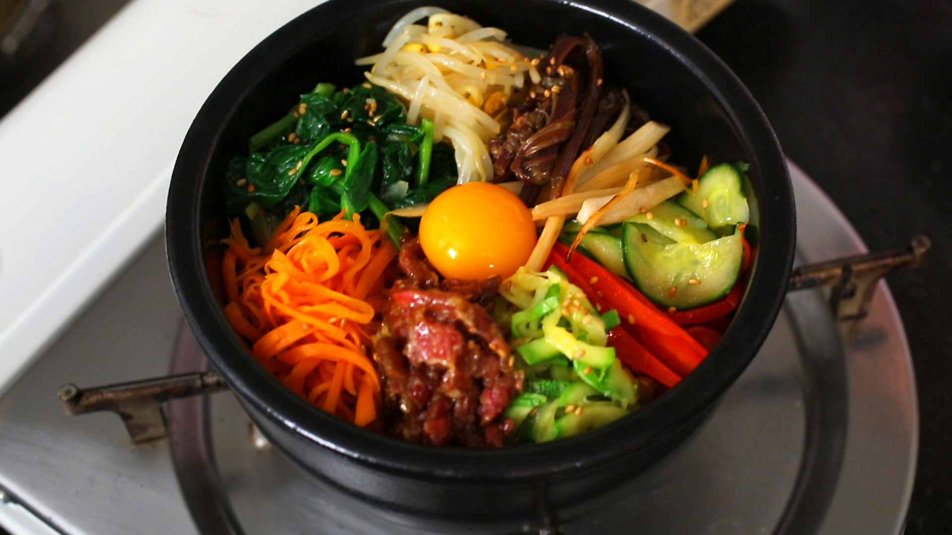 Dolsot-bibimbap in an earthenware bowl (ttukbaegi) or stone pot ...