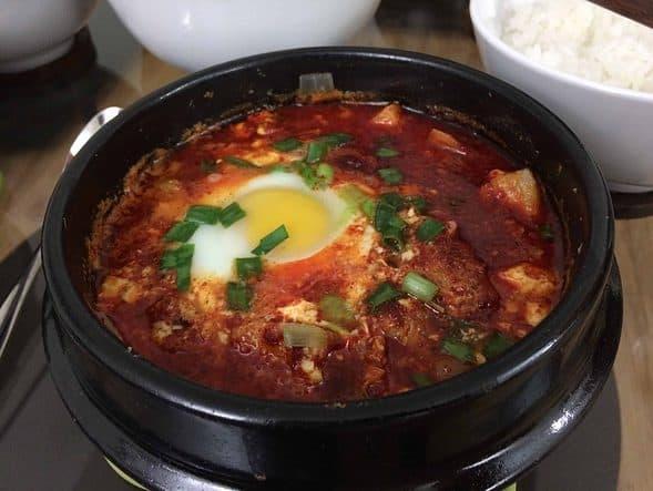Kimchi-sundubu-jjigae in an earthenware bowl (김치순두부찌개)